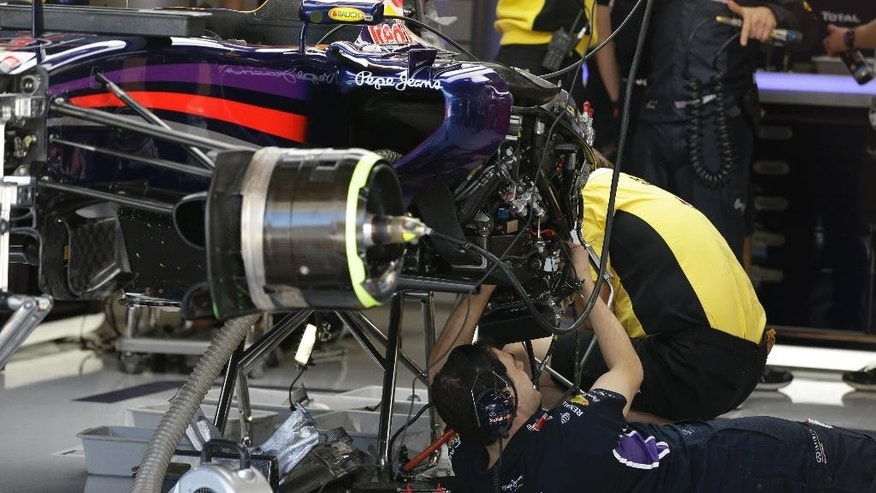A crew member works on the car of Red Bull driver Daniel Ricciardo, of Australia, during the first practice session for the Formula One U.S. Grand Prix auto race at the Circuit of the Americas, Friday, Oct. 31, 2014, in Austin, Texas. (AP Photo/Darron Cummings)