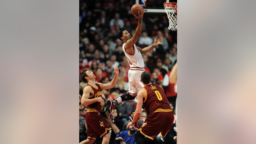 Chicago Bulls' Derrick Rose (1) goes up for a shot against Cleveland Cavaliers' Matthew Dellavedova, left, and Kevin Love (0) during the first half of an NBA basketball game in Chicago, Friday, Oct. 31, 2014. (AP Photo/Paul Beaty)