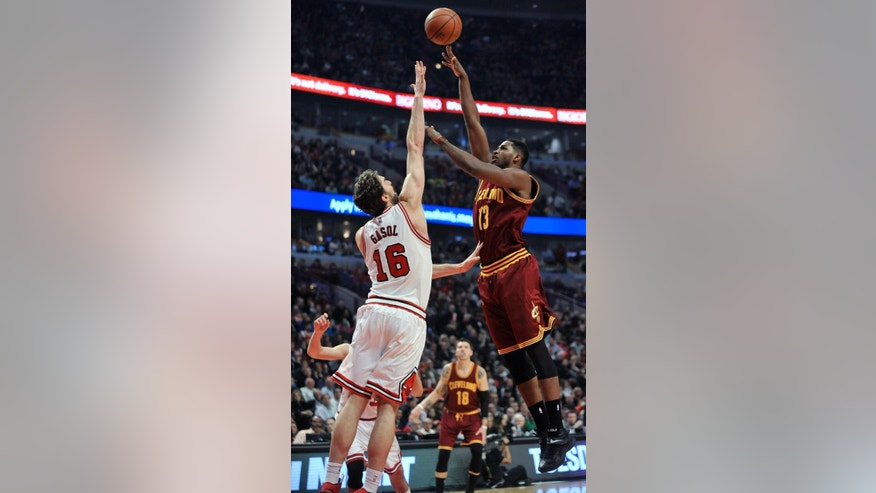 Cleveland Cavaliers' Tristan Thompson (13) releases a shot over Chicago Bulls' Pau Gasol (16) during the first half of an NBA basketball game in Chicago, Friday, Oct. 31, 2014. (AP Photo/Paul Beaty)