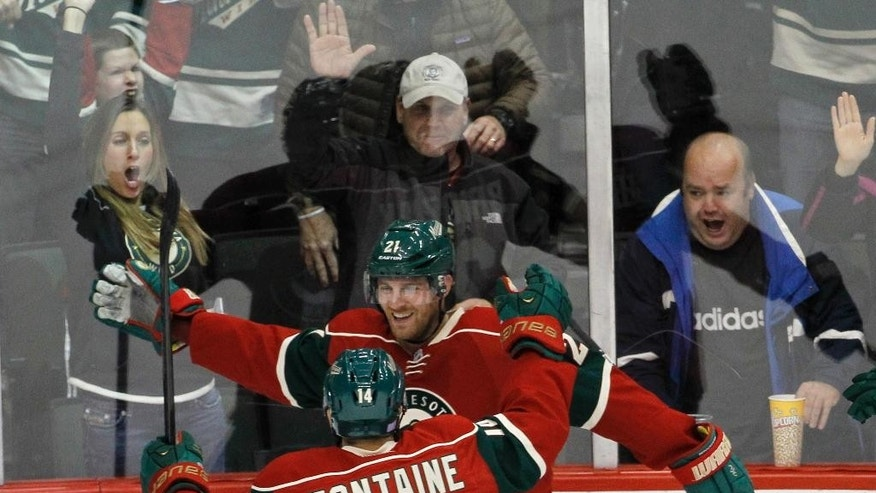 Minnesota Wild center Kyle Brodziak and right wing Justin Fontaine (14) celebrate Brodziak's goal against San Jose Sharks goalie Antti Niemi during the third period of an NHL hockey game in St. Paul, Minn., Thursday, Oct. 30, 2014. The Wild won 4-3 in a shootout. (AP Photo/Ann Heisenfelt)