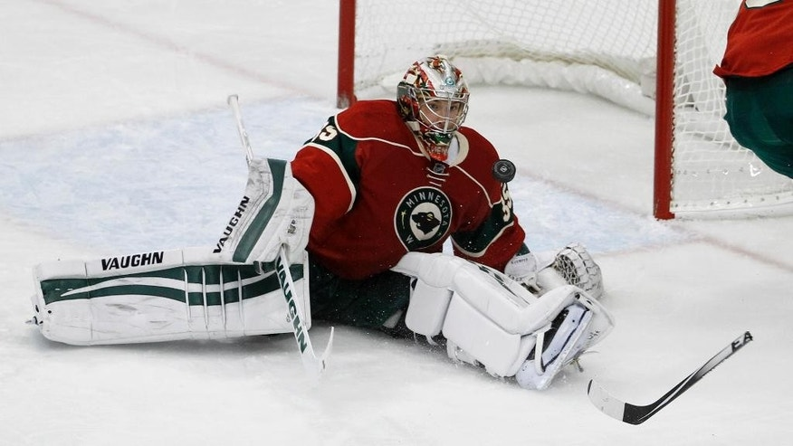 Minnesota Wild goalie Darcy Kuemper (35) deflects a shot by the San Jose Sharks during the first period of an NHL hockey game in St. Paul, Minn., Thursday, Oct. 30, 2014. The Wild won 4-3 in a shootout. (AP Photo/Ann Heisenfelt)