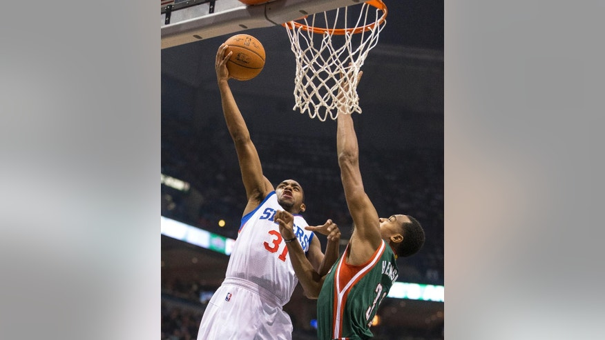 Milwaukee Bucks' John Henson, right, defends the basket as Philadelphia 76ers' Hollis Thompson shoots during the first half of an NBA basketball game Friday, Oct. 31, 2014, in Milwaukee. (AP Photo/Tom Lynn)