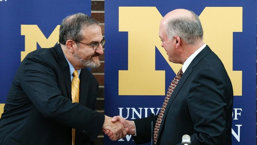 University of Michigan President Mark Schlissel, left, shakes hands with interim athletic director Jim Hackett after a news conference in Ann Arbor, Mich., Friday, Oct. 31, 2014. Hackett, a former Steelcase CEO will replace Dave Brandon who resigned. (AP Photo/Paul Sancya)