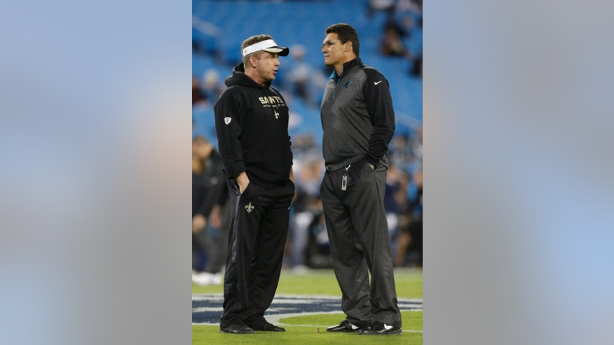 New Orleans Saints head coach Sean Payton, left, speaks with Carolina Panthers head coach Ron Rivera, right, before an NFL football game in Charlotte, N.C., Thursday, Oct. 30, 2014. (AP Photo/Bob Leverone)