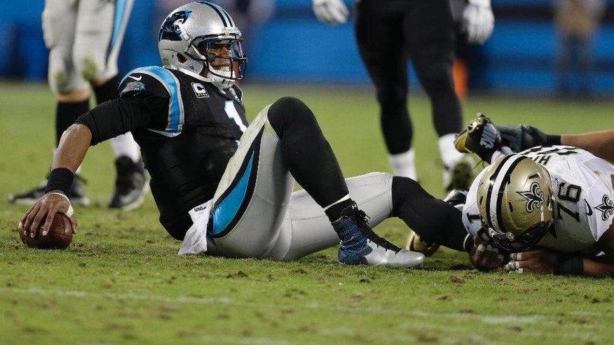Carolina Panthers' Cam Newton (1) reacts after being sacked by New Orleans Saints' Akiem Hicks (76) in the second half of an NFL football game in Charlotte, N.C., Thursday, Oct. 30, 2014. The Saints won 28-10. (AP Photo/Bob Leverone)