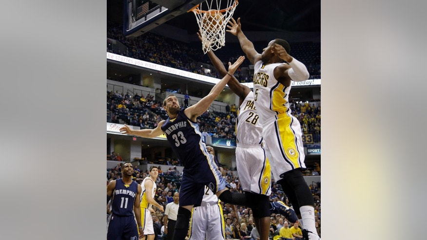 Memphis Grizzlies center Marc Gasol (33) shoots next to Indiana Pacers defenders Ian Mahinmi (28) and Lavoy Allen (5) during the first half of an NBA basketball game in Indianapolis, Friday, Oct. 31, 2014. (AP Photo/AJ Mast)
