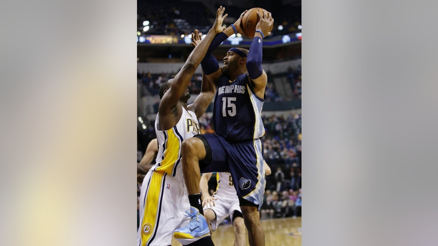 Memphis Grizzlies guard Vince Carter, right, goes up for a shot over Indiana Pacers center Ian Mahinmi during the first half of an NBA basketball game in Indianapolis, Friday, Oct. 31, 2014. (AP Photo/AJ Mast)
