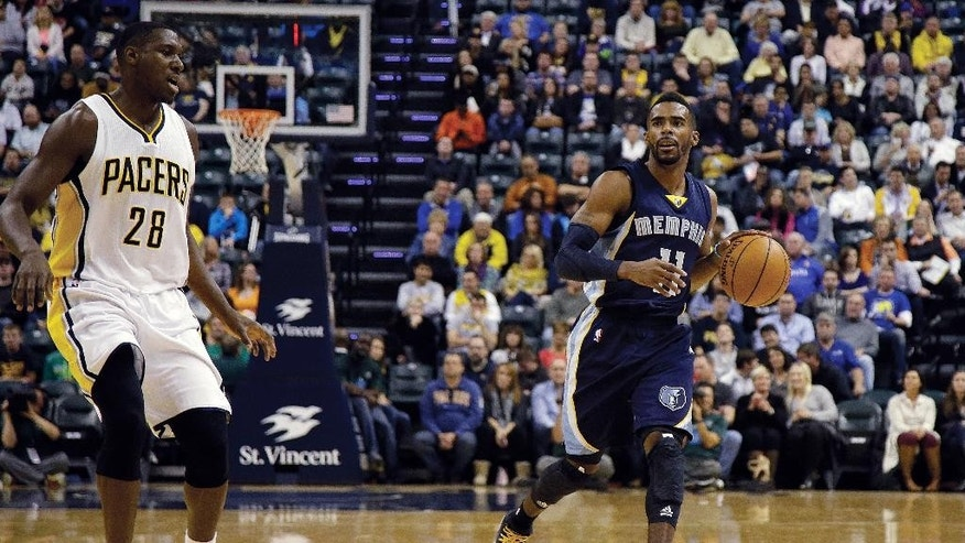 Memphis Grizzlies guard Mike Conley (11) brings the ball up in front of Indiana Pacers center Ian Mahinmi (28) during the first half of an NBA basketball game in Indianapolis, Friday, Oct. 31, 2014. The Grizzlies won 97-89. (AP Photo/AJ Mast)
