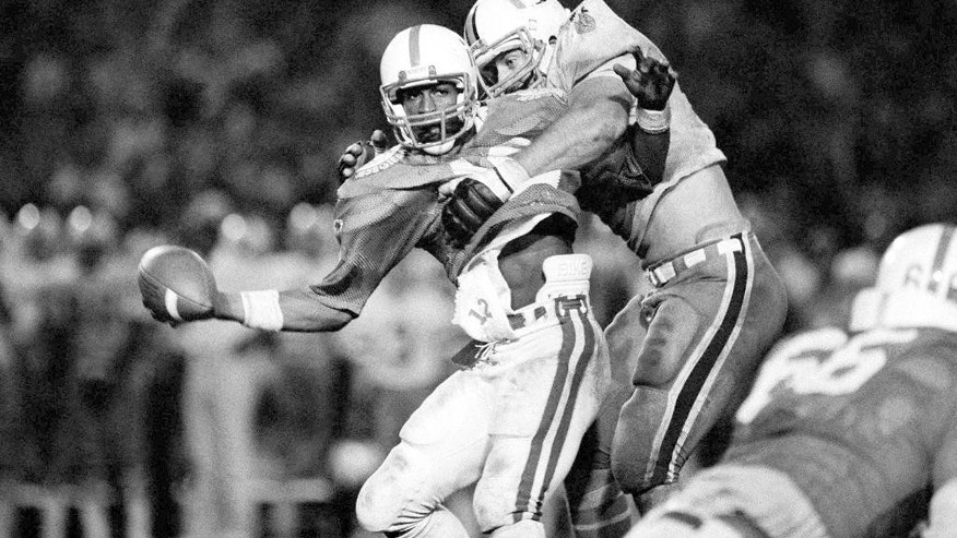 "FILE - In this Jan. 3, 1984, file photo, Nebraska's Turner Gill can't seem to find his receiver as Miami's defensive tackle Kevin Fagan, right, hits him for a loss of 10 yards during the Orange Bowl Classic in Miami where the ""Hurricanes defeated the ""Cornhuskers"" 31-30. Miami sealed the upset and its first national championship by breaking up a pass on a 2-point conversion after Nebraska scored with 48 seconds left. (AP Photo/John Raoux, File)"