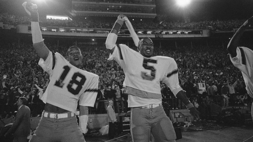 FILE - In this Jan. 3, 1984, file photo, Miami's Tolbert Bain (18) and halfback Melvin Bratton (5) celebrate the win over Nebraska in the 50th Annual Orange Bowl Classic with a score 31-30 in Miami. Miami sealed the upset and its first national championship by breaking up a pass on a 2-point conversion after Nebraska scored with 48 seconds left. (AP Photo/File)