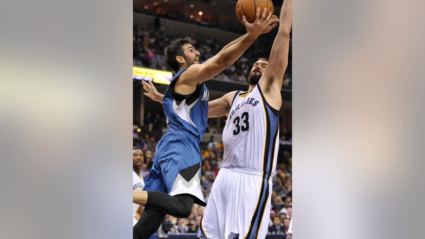 Minnesota Timberwolves guard Ricky Rubio, left, shoots against Memphis Grizzlies center Marc Gasol (33) in the second half of an NBA basketball game Wednesday, Oct. 29, 2014, in Memphis, Tenn. (AP Photo/Brandon Dill)