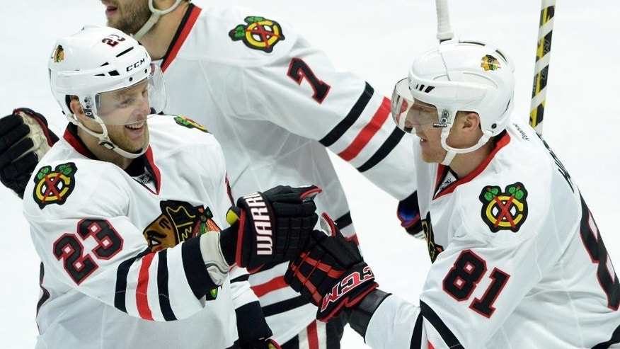 Chicago Blackhawks' Marian Hossa, right, gets a fist-bump from teammate Kris Versteeg as he celebrates his goal  while taking on the Ottawa Senators during NHL hockey game action in Ottawa, Ontario, Thursday, Oct. 30, 2014. (AP Photo/The Canadian Press, Sean Kilpatrick)