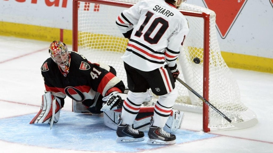 Chicago Blackhawks' Patrick Sharp, right, puts the game-winning shot past Ottawa Senators' Craig Anderson during shootout NHL hockey game action in Ottawa, Ontario, Thursday, Oct. 30, 2014 (AP Photo/The Canadian Press, Sean Kilpatrick)