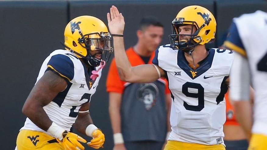 West Virginia quarterback Clint Trickett (9) congratulates Dreamius Smith (2) following his touchdown during the fourth quarter of an NCAA college football game against Oklahoma State in Stillwater, Okla., Saturday, Oct. 25, 2014. West Virginia won 34-10.(AP Photo/Sue Ogrocki)