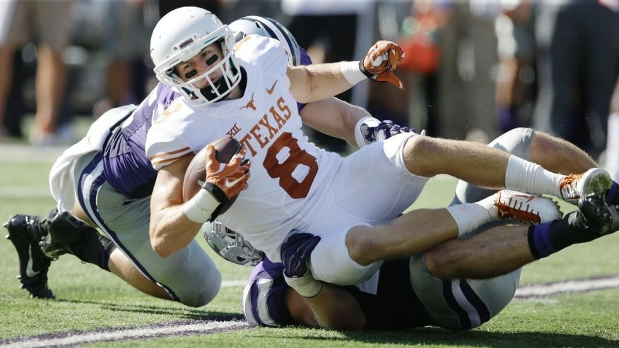 Texas wide receiver Jaxon Shipley (8) is tackled by Kansas State linebackers Jonathan Truman, bottom, and Will Davis, back left, during the second half of an NCAA college football game in Manhattan, Kan., Saturday, Oct. 25, 2014. Kansas State defeated Texas 23-0. (AP Photo/Orlin Wagner)