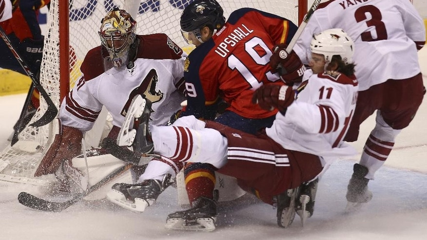 Arizona Coyotes' goalie Mike Smith (41) and Martin Hanzal (11) try to keep Florida Panthers' Scottie Upshall (19) away from the puck during the first period of an NHL hockey game in Sunrise, Fla., Thursday, Oct. 30, 2014. (AP Photo/J Pat Carter)