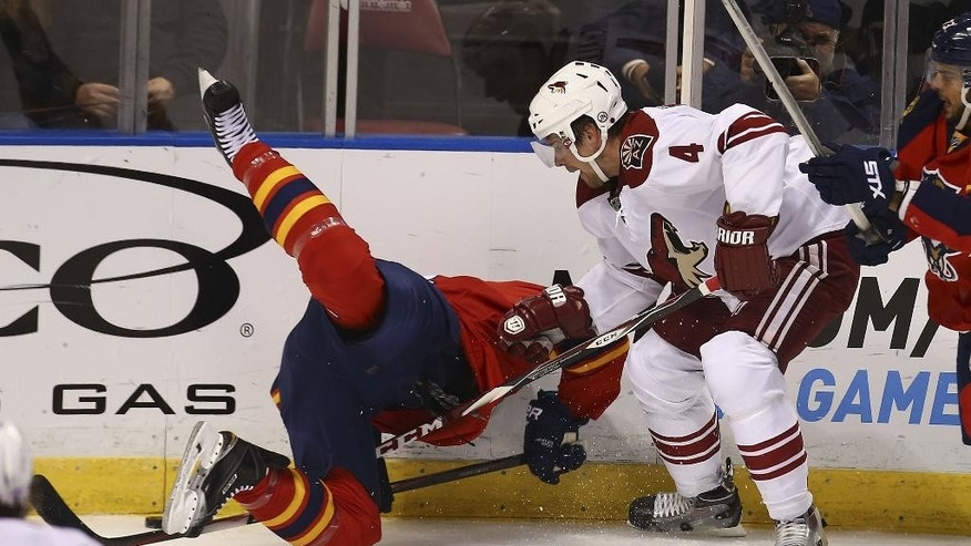 Florida Panthers' Tomas Fleischmann and Arizona Coyotes' Zbynek Mikchalek (4) battle for the puck during the first period of an NHL hockey game in Sunrise, Fla., Thursday, Oct. 30, 2014. (AP Photo/J Pat Carter)