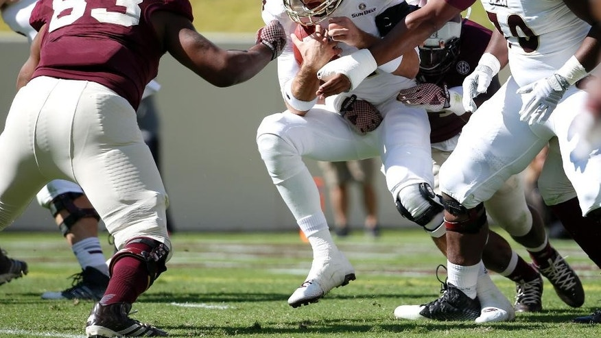 Louisiana Monroe quarterback Pete Thomas (14) is sacked by Texas A&M defensive lineman Hardreck Walker, rear, as Alonzo Williams (83) assist on the play in the first half of an NCAA college football game, Saturday, Nov. 1, 2014, in College Station, Texas. (AP Photo/Tony Gutierrez)