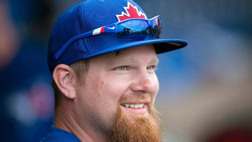 FILE - In this Feb. 26, 2014, file phot, Toronto Blue Jays' Adam Lind smiles on the bench during spring training baseball in Clearwater, Fla. Lind was traded from the Blue Jays to the Milwaukee Brewers on Saturday, Nov. 1, 2014, for right-hander Marco Estrada, ending the first baseman's nine-year run in Toronto. (AP Photo/The Canadian Press, Frank Gunn, File-