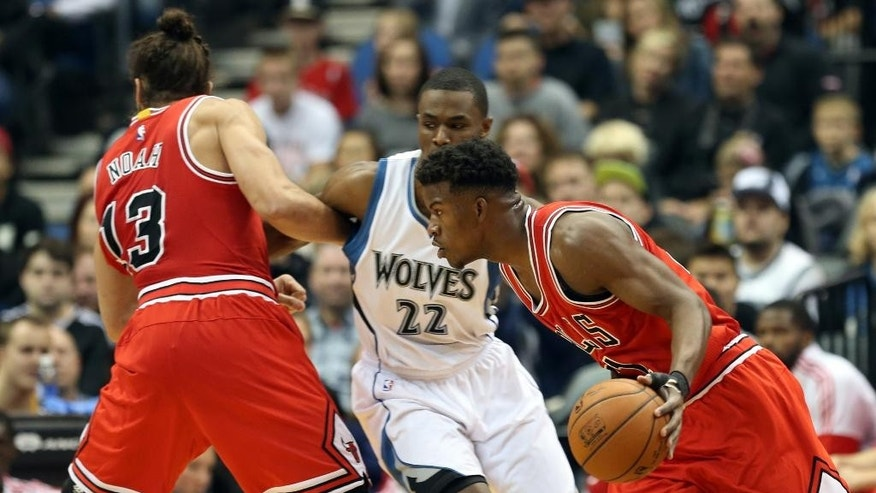 Chicago Bulls' Joakim Noah , left, keeps Minnesota Timberwolves' Andrew Wiggins, center, tied up as Bulls' Jimmy Butler drives the ball in the first quarter of an NBA basketball game, Saturday, Nov. 1, 2014, in Minneapolis. (AP Photo/Jim Mone)