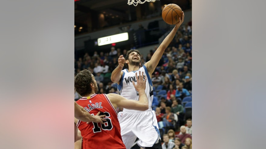 Minnesota Timberwolves' Ricky Rubio, right, of Spain, lays up a shot as Chicago Bulls' Pau Gasol of Spain watches in the first quarter of an NBA basketball game, Saturday, Nov. 1, 2014, in Minneapolis. (AP Photo/Jim Mone)