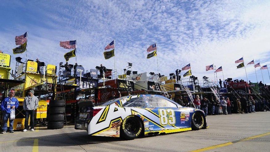 NASCAR Fans line up in the garage area to see race cars during practice at the Texas Motor Speedway in Fort Worth, Texas, Saturday, Nov. 1, 2014. Deep in the heart of Texas on Sunday, NASCAR and Formula One will have races going on at the same time. The scenes about 220 miles apart are drastically different. (AP Photo/Ralph Lauer)