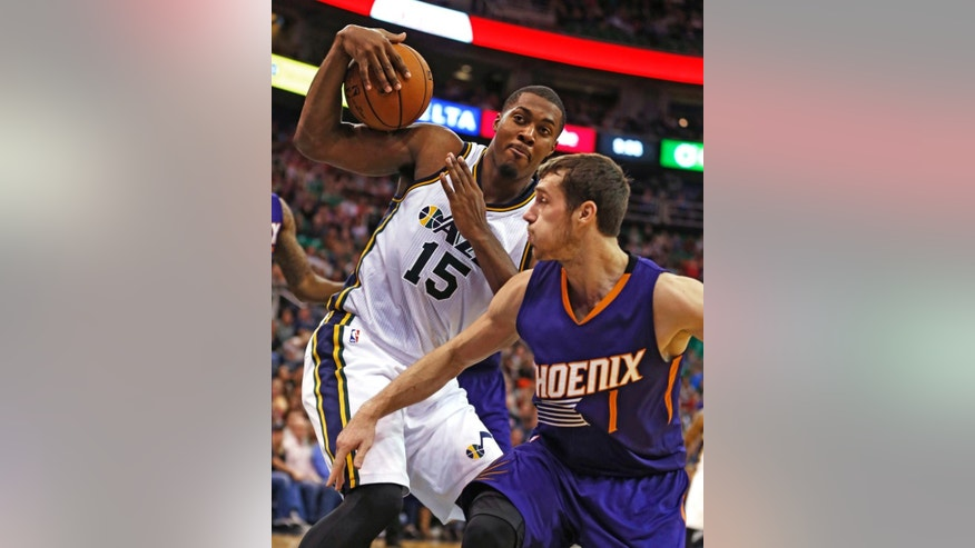 Utah Jazz' Derrick Favors, left, grabs a rebound from Phoenix Suns' Goran Dragic during the second half of an NBA basketball game in Salt Lake City, Saturday, Nov. 1, 2014. The Jazz defeated the Suns 118-91. (AP Photo/George Frey)