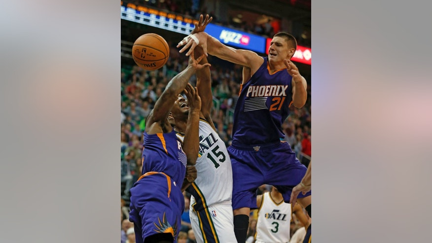 Phoenix Suns' Alex Len, right, Eric Bledsoe, left, and Utah Jazz' Derrick Favors fight for a rebound during the first half of an NBA basketball game in Salt Lake City, Saturday, Nov. 1, 2014. (AP Photo/George Frey)