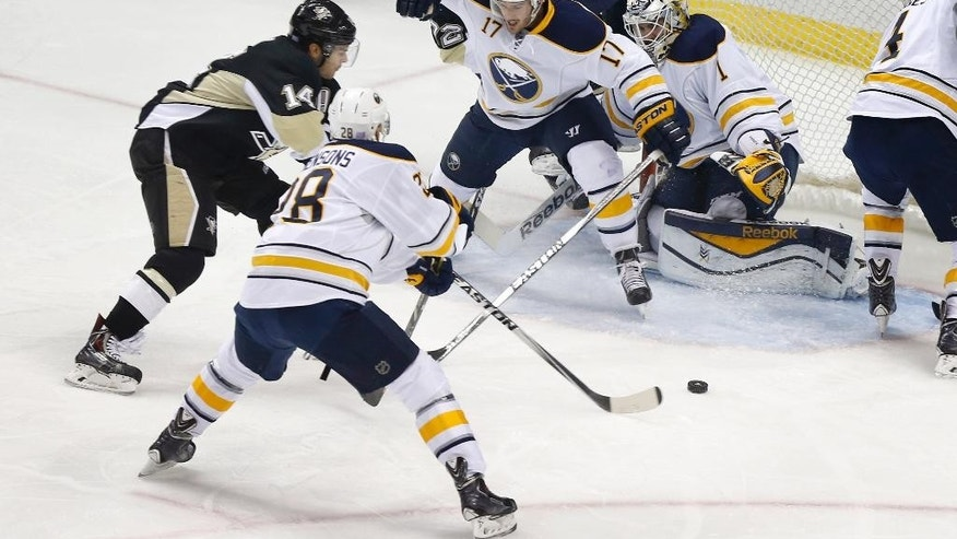 Pittsburgh Penguins' Chris Kunitz (14) gets between Buffalo Sabres' Zemgus Girgensons (28) and Torrey Mitchell (17) to score a goal on goalie Jhonas Enroth (1) in the first period of an NHL hockey game, Saturday, Nov. 1, 2014 in Pittsburgh. (AP Photo/Keith Srakocic)
