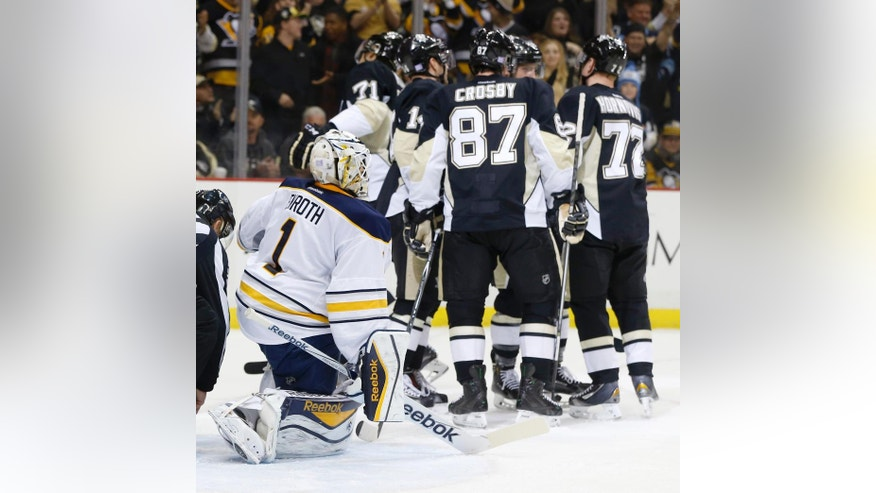 Buffalo Sabres goalie Jhonas Enroth (1) kneels in the crease as Pittsburgh Penguins' Patric Hornqvist celebrates with Sidney Crosby (87) and other teammates after scoring during the second period of an NHL hockey game, Saturday, Nov. 1, 2014 in Pittsburgh. (AP Photo/Keith Srakocic)