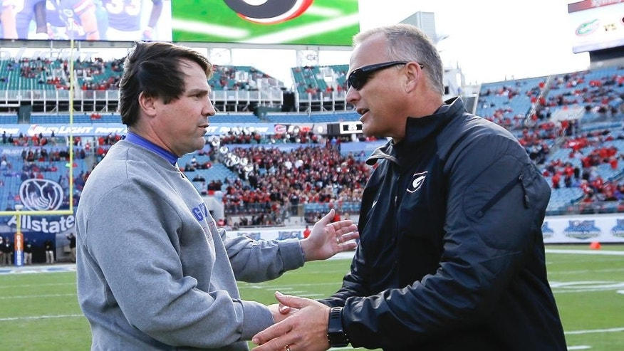 Florida head coach Will Muschamp left, and Georgia head coach Mark Richt, right, shake hands at midfield before the start of a NCAA college football game in Jacksonville, Fla., Saturday, Nov. 1, 2014. (AP Photo/Stephen B. Morton)
