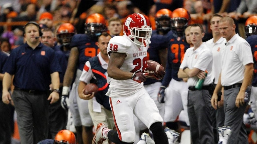 North Carolina State's Jaylen Samuels runs past Syracuse players in the third quarter of an NCAA college football game against in Syracuse, N.Y., Saturday, Nov. 1, 2014. North Carolina State won 24-17. (AP Photo/Nick Lisi)