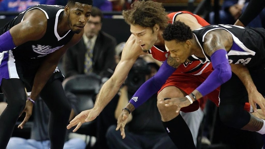 Portland Trail Blazers center Robin Lopez, center, and Sacramento Kings guard Ben McLemore, right, dive for the ball as Kings forward Jason Thompson, left, looks on during the first quarter of an NBA basketball game in Sacramento, Calif. Friday, Oct. 31, 2014.(AP Photo/Rich Pedroncelli)