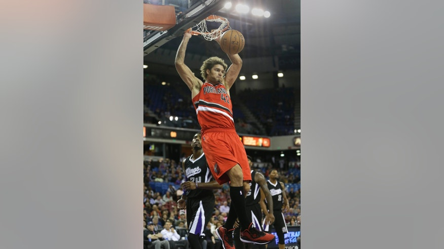 Portland Trail Blazers center Robin Lopez hangs on the rim after stuffing over Sacramento Kings forward Jason Thompson, left, during the first quarter of an NBA basketball game in Sacramento, Calif. Friday, Oct. 31, 2014.(AP Photo/Rich Pedroncelli)