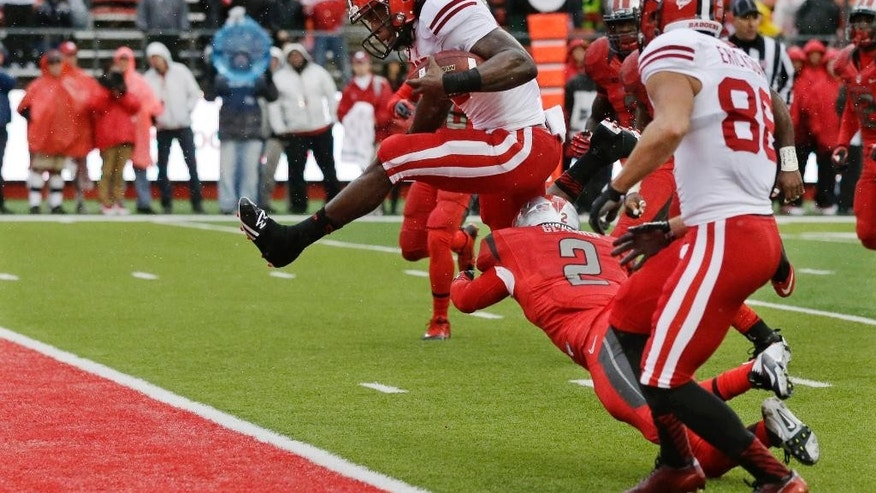 Wisconsin running back Melvin Gordon (25) leaps for a touchdown over Rutgers defensive back Gareef Glashen (2) during the first half of an NCAA college football game against Rutgers, Saturday, Nov. 1, 2014, in Piscataway, N.J.  (AP Photo/Mel Evans)