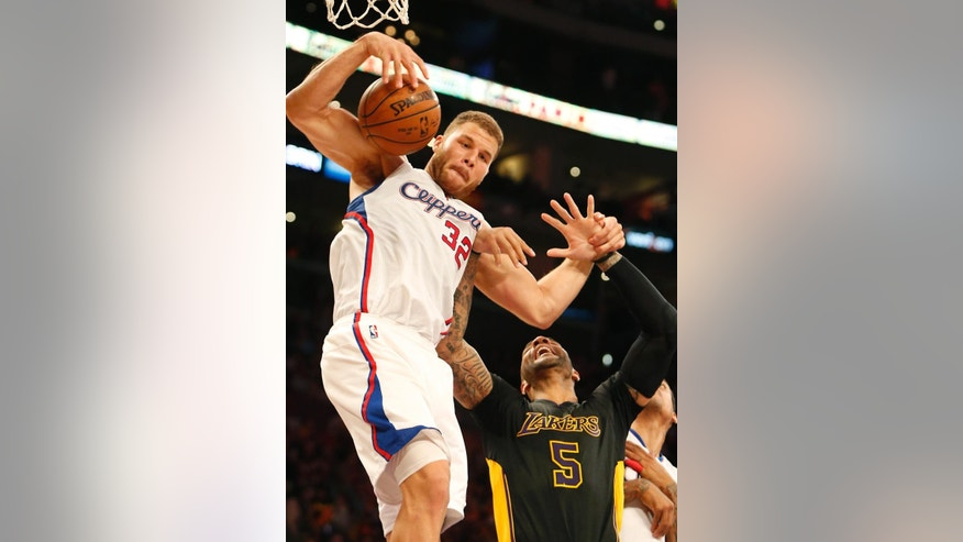 Los Angeles Clippers' Blake Griffin pulls down a rebound ahead of Los Angeles Lakers' Carlos Boozer in the first half of an NBA basketball game in Los Angeles on Friday, Oct. 31, 2014. (AP Photo/Christine Cotter)