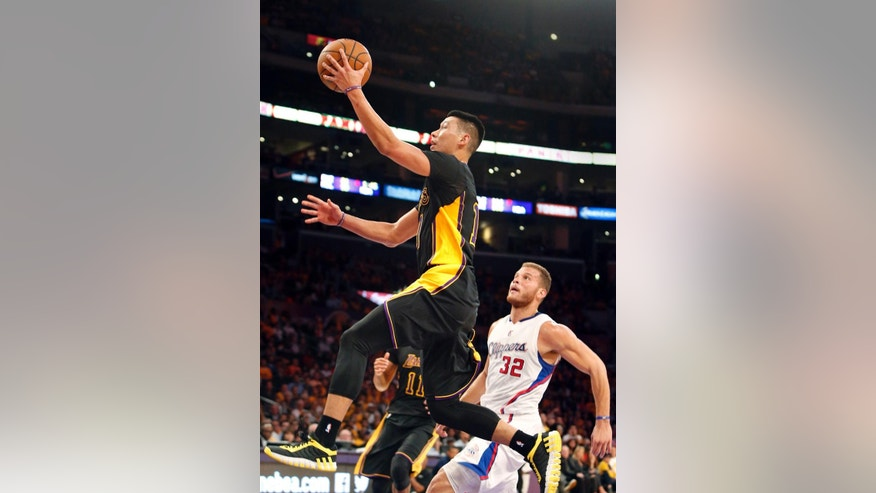 Los Angeles Lakers' Jeremy Lin, left, goes to the basket as Los Angeles Clippers' Blake Griffin looks on in the first half of an NBA basketball game in Los Angeles on Friday, Oct. 31, 2014. (AP Photo/Christine Cotter)
