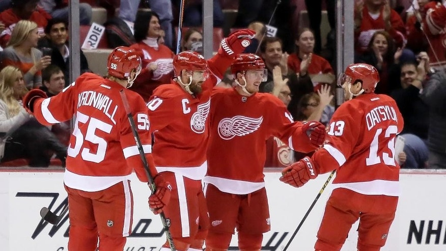 Detroit Red Wings' Gustav Nyquist (14), of Sweden, second from right, celebrates his first period goal against the Los Angeles Kings with teammates Niklas Kronwall (55), of Sweden, Henrik Zetterberg, of Sweden, and Pavel Datsyuk (13), of Russia, during an NHL hockey games Friday, Oct. 31, 2014, in Detroit. (AP Photo/Duane Burleson)
