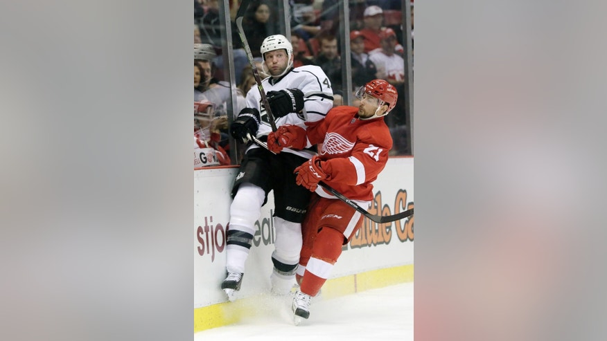 Los Angeles Kings' Robyn Regehr (44), of Brazil, is checked against the boards by Detroit Red Wings' Tomas Tatar (21), of Slovakia, during the second period of an NHL hockey games Friday, Oct. 31, 2014, in Detroit. (AP Photo/Duane Burleson)