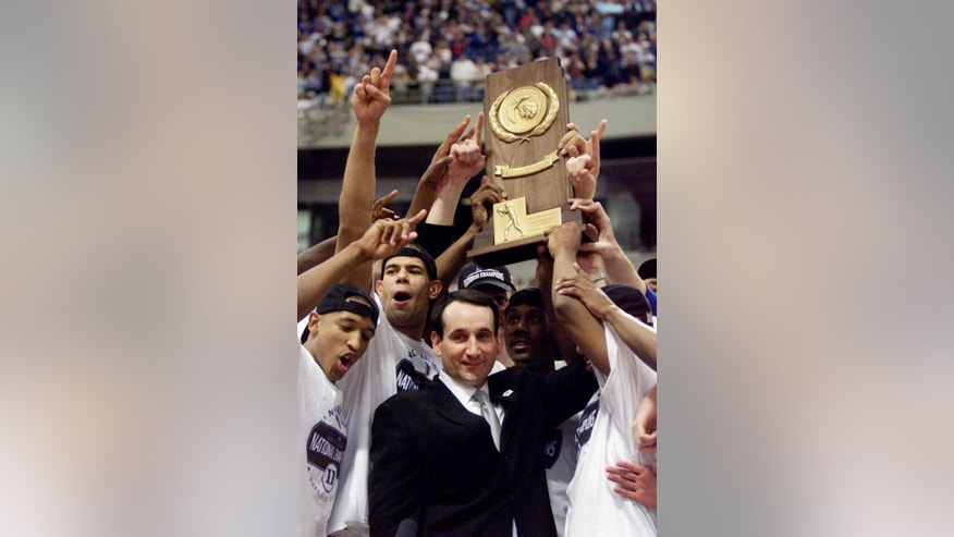 ADVANCE FOR WEEKEND EDITIONS, NOV. 1-2 - FILE - In this April 2, 2001, file photo, Duke head coach Mike Krzyzewski and his Blue Devils hoist the championship trophy after beating Arizona 82-72 in the finals of the Final Four in Minneapolis. The Atlantic Coast Conference had an impressive enough roster of Naismith Hall of Fame coaches before expansion with Duke's Mike Krzyzewski and North Carolina's Roy Williams. Then it added Syracuse's Jim Boeheim last year, and now is bringing in Louisville's Rick Pitino. It's a group with nine NCAA championships combined and now they're going to be fighting each other for an ACC title. (AP Photo/Bob Jordan, File)