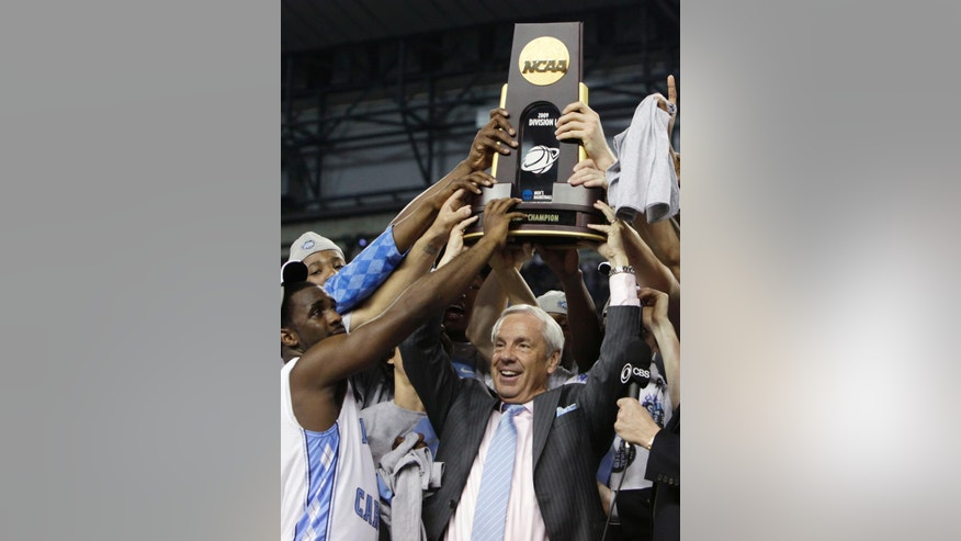 ADVANCE FOR WEEKEND EDITIONS, NOV. 1-2 - FILE - In this April 7, 2009, file photo, North Carolina head coach Roy Williams, center, celebrates with his team after their 89-72 victory over Michigan State in the championship game at the men's NCAA Final Four college basketball tournament in Detroit. The Atlantic Coast Conference had an impressive enough roster of Naismith Hall of Fame coaches before expansion with Duke's Mike Krzyzewski and North Carolina's Roy Williams. Then it added Syracuse's Jim Boeheim last year, and now is bringing in Louisville's Rick Pitino. It's a group with nine NCAA championships combined and now they're going to be fighting each other for an ACC title.  (AP Photo/Paul Sancya, File)