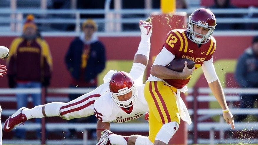 Iowa State quarterback Sam B. Richardson (12) runs from Oklahoma linebacker Jordan Evans during the second half of an NCAA college football game, Saturday, Nov. 1, 2014, in Ames, Iowa. Oklahoma won 59-14. (AP Photo/Charlie Neibergall)