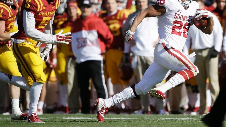 Oklahoma running back Alex Ross (28) runs from Iowa State defensive back Kamari Cotton-Moya, left, during the first half of an NCAA college football game, Saturday, Nov. 1, 2014, in Ames, Iowa. Oklahoma won 59-14. (AP Photo/Charlie Neibergall)
