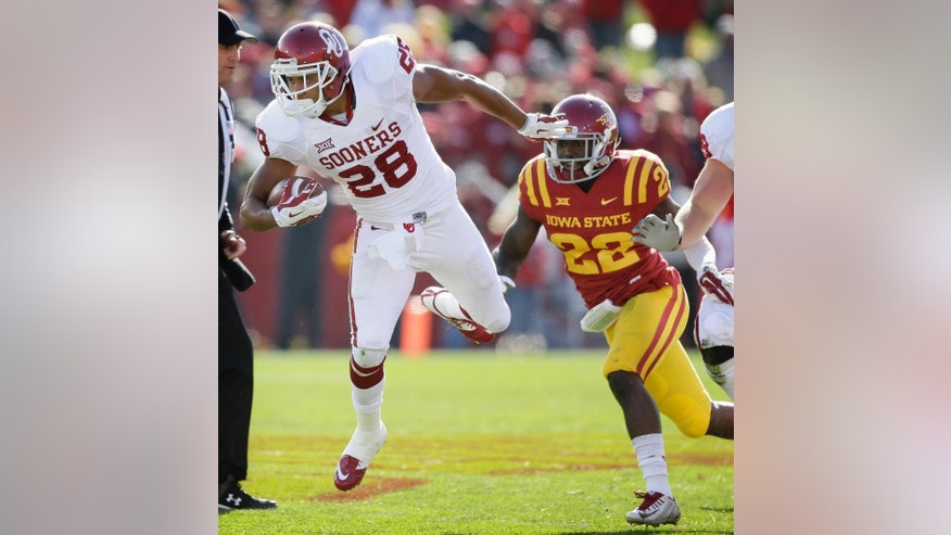 Oklahoma running back Alex Ross (28) runs from Iowa State defensive back T.J. Mutcherson (22) during the first half of an NCAA college football game, Saturday, Nov. 1, 2014, in Ames, Iowa. Oklahoma won 59-14. (AP Photo/Charlie Neibergall)