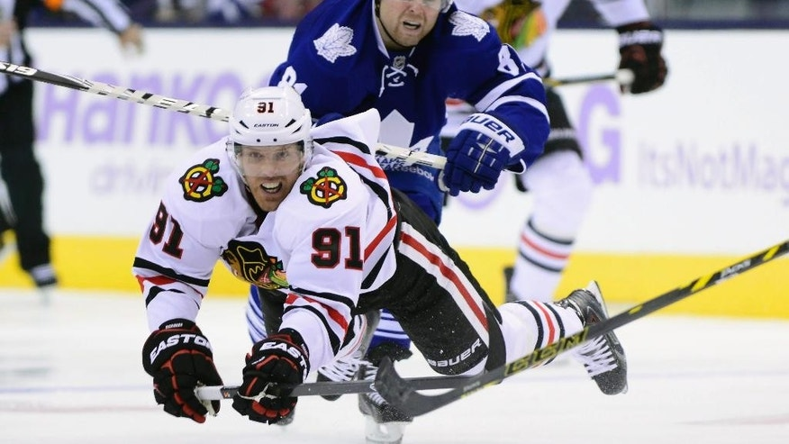 Toronto Maple Leafs forward Phil Kessel (81) collides with Chicago Blackhawks forward Brad Richards (91) during the third period of an NHL hockey game in Toronto on Saturday, Nov. 1, 2014. (AP Photo/The Canadian Press, Frank Gunn)