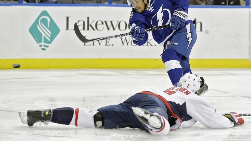 Tampa Bay Lightning right wing J.T. Brown (23) shoots over Washington Capitals defenseman Matt Niskanen (2) during the second period of an NHL hockey game Saturday, Nov. 1, 2014, in Tampa, Fla. (AP Photo/Chris O'Meara)