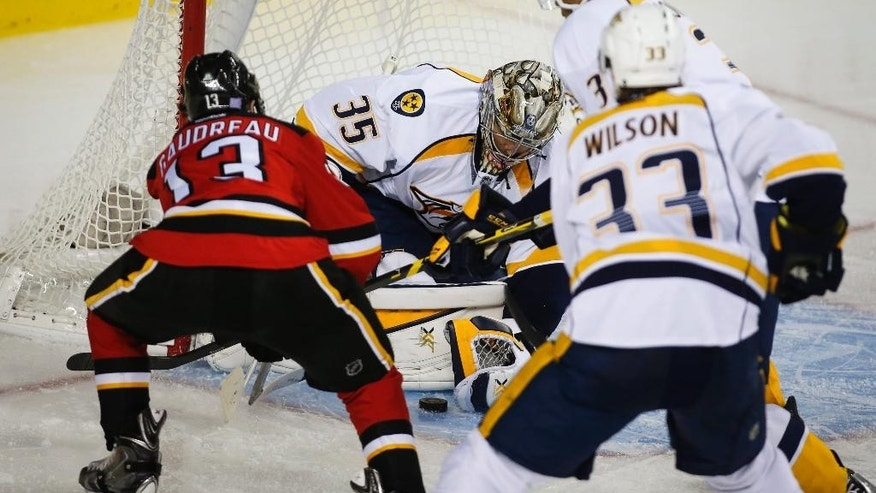 Nashville Predators goalie Pekka Rinne, from Finland, pounces on the puck as Calgary Flames Johnny Gaudreau, left, tries to score during the third period of an NHL hockey game Friday, Oct. 31, 2014, in Calgary, Alberta. (AP Photo/The Canadian Press, Jeff McIntosh)