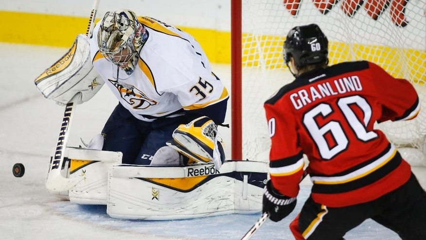 Nashville Predators goalie Pekka Rinne, left, from Finland, swats away a shot from Calgary Flames' Markus Granlund, from Finland, during the second period of an NHL hockey game Friday, Oct. 31, 2014, in Calgary, Alberta. (AP Photo/The Canadian Press, Jeff McIntosh)