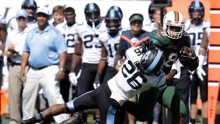 Miami running back Duke Johnson (8) runs for a first down as North Carolina safety Dominquie Green (26) defends during the first half of an NCAA football game, Saturday, Nov. 1, 2014, in Miami Gardens, Fla. (AP Photo/Lynne Sladky)