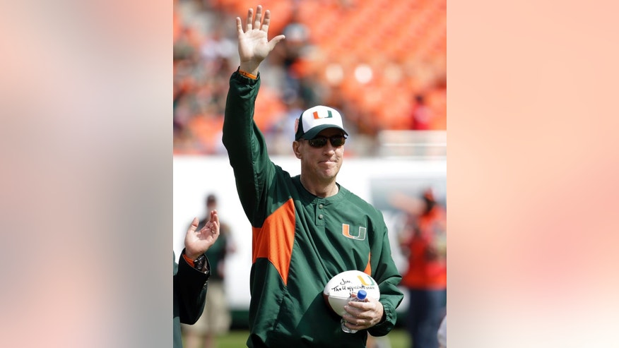 Former Miami quarterback Jim Kelly waves after being presented with a game ball as he is named honorary captain before an NCAA football game against North Carolina, Saturday, Nov. 1, 2014, in Miami Gardens, Fla. Kelly also was an NFL quarterback with the Buffalo Bills. (AP Photo/Lynne Sladky)